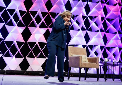 LAS VEGAS, NV - APRIL 10: Former Secretary of State Hillary Clinton ducks after a woman threw an object toward her while she was delivering remarks at the Institute of Scrap Recycling Industries conference on April 10, 2014 in Las Vegas, Nevada. Clinton is continuing on a speaking tour this week with the stop at the recycling industry trade conference. (Photo by Isaac Brekken/Getty Images)