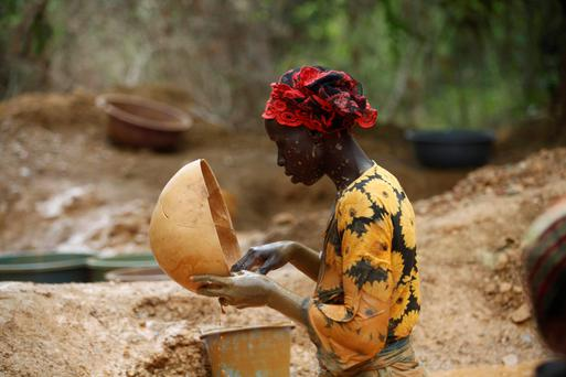 A prospector pans for gold. Photo: Reuters/Luc Gnago