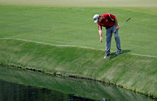 Louis Oosthuizen, of South Africa, looks for his ball in the water off the 15th green during the second round of the Masters golf tournament Friday, April 11, 2014, in Augusta, Ga. (AP Photo/Matt Slocum)