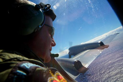 Sgt. Trent Wyatt, a crew member of a Royal New Zealand Air Force P-3 Orion, look out in the search for the missing Malaysia Airlines Flight MH370 over the Indian Ocean, Friday, April 11, 2014. (AP Photo/Richard Wainwright, Pool)