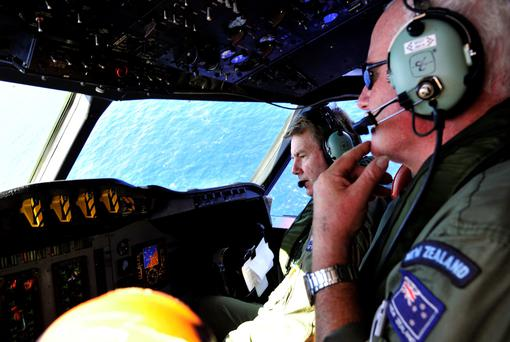 Royal New Zealand Air Force (RNZAF) co-pilot squadron leader Brett McKenzie, left, and Flight Engineer Trent Wyatt sit in the cockpit aboard a P-3 Orion on route to search over the southern Indian Ocean looking for missing Malaysia Airlines flight MH370 Friday, April 11, 2014. (AP Photo/Richard Polden, Pool)