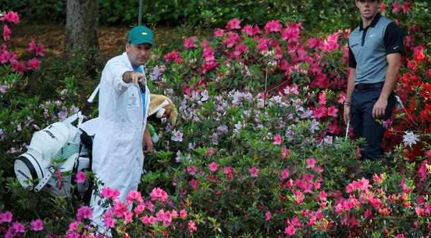 Rory McIlroy consults with his caddie before hitting from the azaleas on the 13th hole during the second round of the Masters at Augusta.