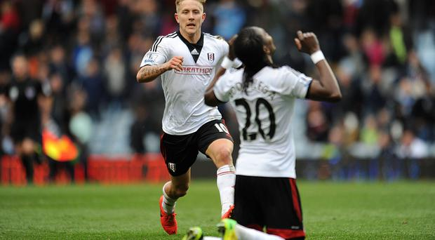 Fulham's Hugo Rodallega and Lewis Holtby after Rodallega opened the scoring at Carrow Road.