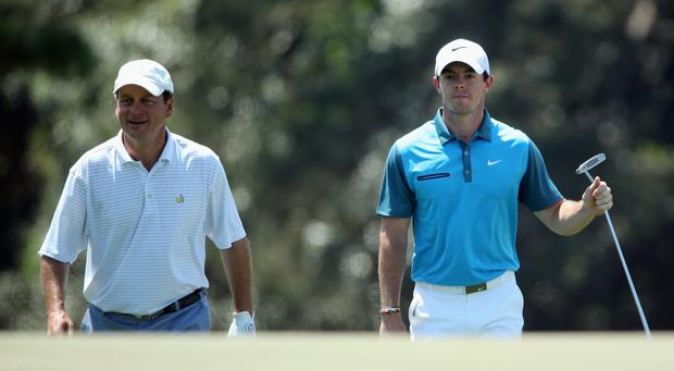 Marker Jeff Knox and Rory McIlroy of Northern Ireland walk to the 18th green during the third round of the 2014 Masters Tournament at Augusta