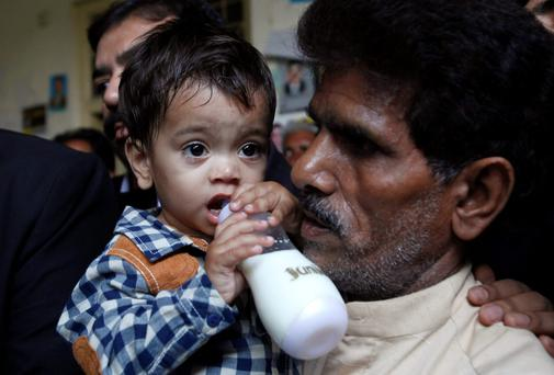 Nine-month-old Musa Khan drinks milk from his bottle while being carried by his grandfather Muhammad Yasin as they leave after appearing in a court in Lahore, Pakistan. A judge threw out charges of attempted murder against the baby on Saturday.