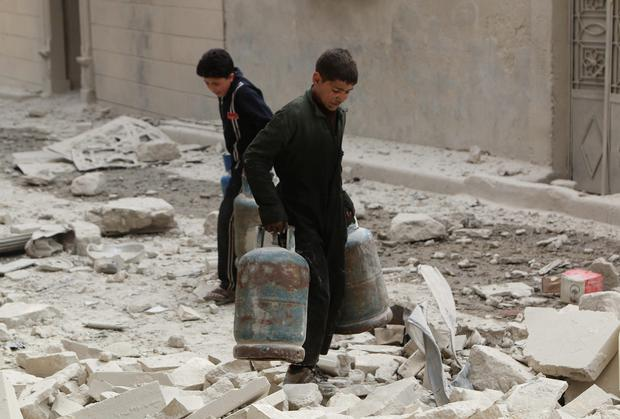 Boys carry gas cylinders over debris and damage after what activists said was shelling from forces loyal to Syria's President Bashar al-Assad in the Al-Maysar neighbourhood of Aleppo April 12, 2014. REUTERS/Hosam Katan (SYRIA - Tags: POLITICS CIVIL UNREST CONFLICT)