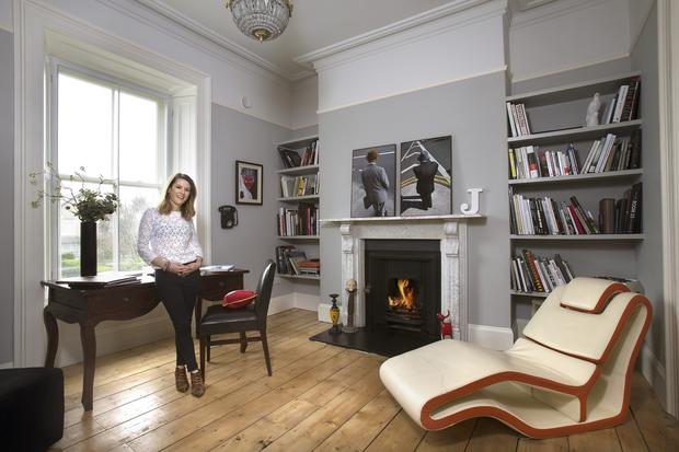 Carla in the front living room at ground-floor level. The mantelpiece is original to the house. The photographs above it are by a college friend of Jason's. Carla trained in graphic design, and throughout the home there are signs with mottoes, such as 'God is in the details' and the large J on the mantelpiece