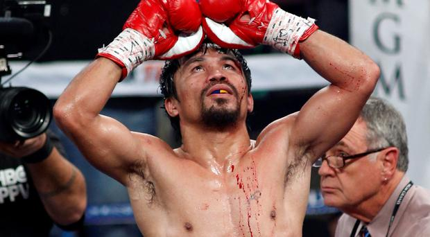 Manny Pacquiao celebrates his unanimous decision victory over WBO welterweight champion Timothy Bradley at the MGM Grand Garden Arena Las Vegas.