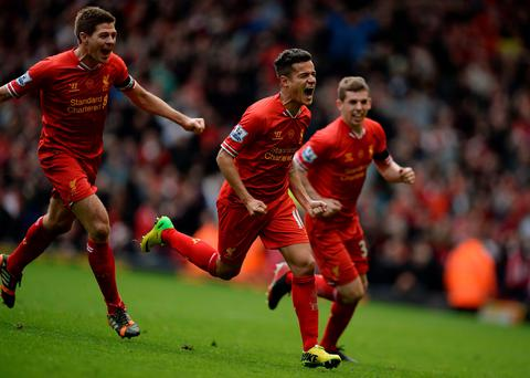 Philippe Courtinho celebrates scoring with Jon Flanagan and Steven Gerrard against Manchester City at Anfield.