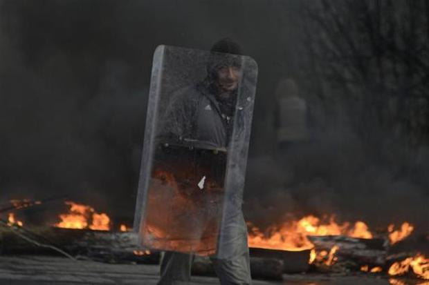 A pro-Russian protester holds a shield at a check point, with black smoke from burning tyres rising above, in Slaviansk April 13, 2014. REUTERS/Maks Levin