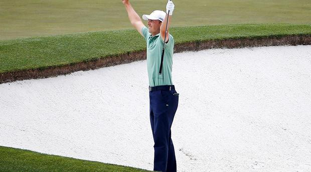 Jordan Spieth celebrates after chipping in for a birdie from a bunker on the forth hole at Augusta