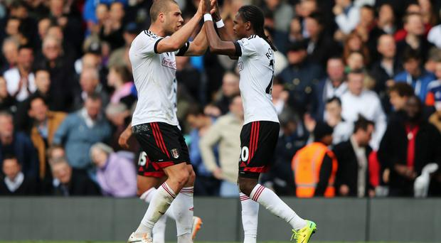 Hugo Rodallega celebrates with Pajtim Kasami after his strike gave Fulham a vital three points in their basement battle with Norwich City