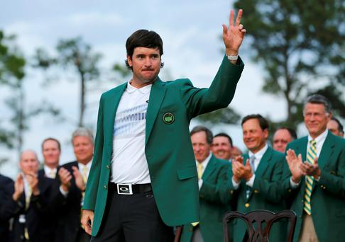 Masters champion Bubba Watson of the U.S. waves after receiving the traditional green jacket following the final round of the Masters golf tournament at the Augusta National Golf Club in Augusta, Georgia April 13, 2014.