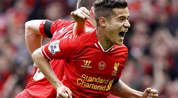 Liverpool's Phillippe Coutinho celebrates after he scores his teams third goal during the Barclays Premier League match at Anfield. Photo: PA
