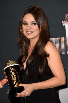 Actress Mila Kunis poses with the Best Villain award for 'Oz The Great and Powerful' in the press room during the 2014 MTV Movie Awards at Nokia Theatre L.A. Live on April 13, 2014 in Los Angeles, California. (Photo by Jason Merritt/Getty Images for MTV)