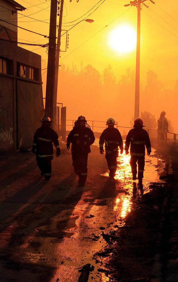 Firefighters walk past an area where a forest fire burned several neighbourhoods in the hills in Valparaiso city. Photo: Retuers/Carlos Gutierrez