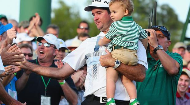 Bubba Watson of the United States holds his son Caleb after winning the 2014 Masters