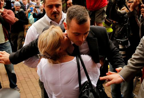Oscar Pistorius is hugged by a supporter as he arrives ahead of his trial at the North Gauteng High Court in Pretoria. Photo: Reuters