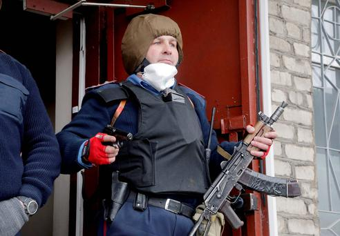 The head of the local police station Herman Pristupa, brandishes firearms at the entrance to a police headquarters stormed by pro-Russian activists in Horlivka, Ukraine last month