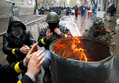 Pro-Russian men gather around a fire at a barricade near the police headquarters in Slaviansk. Photo: Reuters