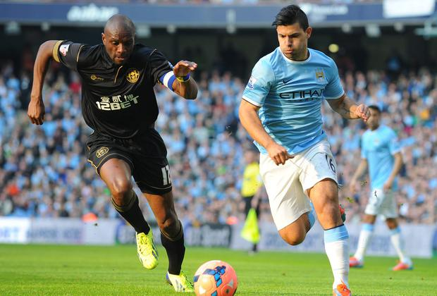 Wigan Athletic's Emmerson Boyce (L) vies with Manchester City's Sergio Aguero (R)