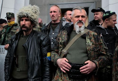 Self defense volunteers line up outside the Parliament in Kiev, Ukraine, Tuesday, April 15, 2014.