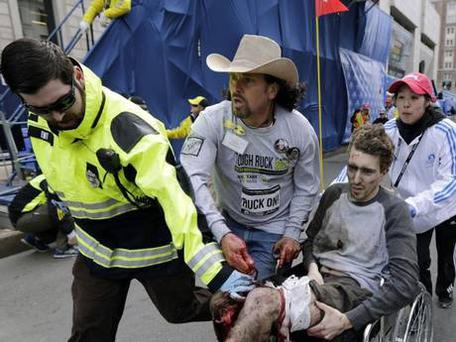 Paul Mitchell, left, bystander Carlos Arredondo, in cowboy hat, and Boston University student Devin Wang push Jeff Bauman in a wheelchair after he was injured in one of two explosions near the finish line of the Boston Marathon.