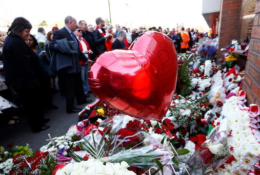Fans lay flowers by the Shankly gates before a memorial service to mark the 25th anniversary of the Hillsborough disaster at Anfield in Liverpool