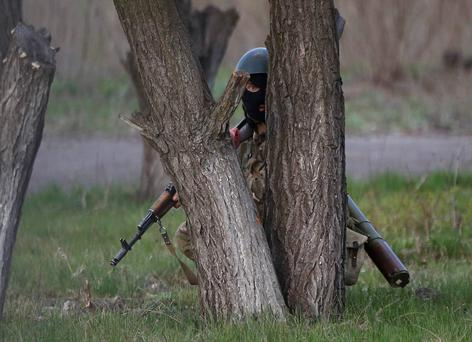An Ukrainian soldier takes cover behind a tree as pro-Russia protesters gathered in front of a Ukrainian airbase in Kramatorsk, in eastern Ukraine April 15, 2014. Ukrainian armed forces on Tuesday launched a