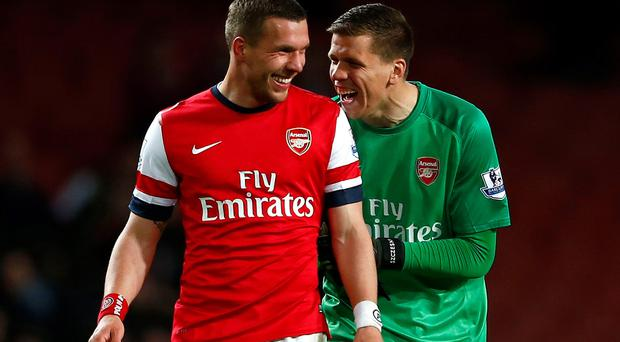 Arsenal's Lukas Podolski (L) and team mate Wojciech Szczesny react after their English Premier League soccer match against West Ham United at the Emirates