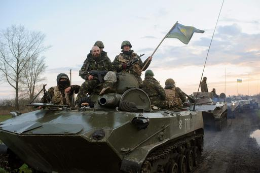 Ukrainian soldiers sit on top of military vehicles with Ukrainian national flags in a field about 70 kilometers (44 miles) from the eastern Ukrainian town of Slovyansk, where the Ukrainian regional administration building was seized by pro-Russian activists. A deadline set by the Ukrainian government for pro-Russian gunmen to leave government buildings in eastern Ukraine and surrender weapons passed without incident early Monday, with no immediate sign of any action to liberate any seized buildings. Photo: AP
