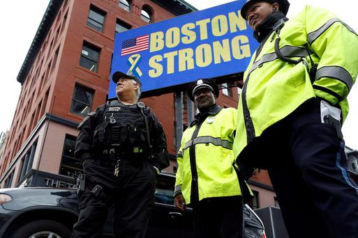 Boston Police stand beneath a Boston Strong sign near the site of one of the two bomb blasts on the one-year anniversary of the 2013 Boston Marathon bombings in Boston, Massachusetts. Reuters/Dominick Reuter