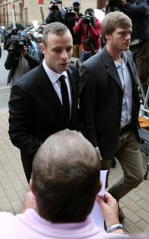 Oscar Pistorius, left, arrives with an unidentified relative as he acknowledges a supporter outside the high court in Pretoria, South Africa. AP Photo/Themba Hadebe