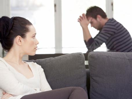 Young woman sitting on sofa, looking at distressed man at table couple fight argue disagreement depressed depression marriage divorce anxiety msnbc stock photo photography