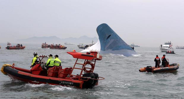 "Part of South Korean passenger ship ""Sewol"" that has been sinking is seen as South Korean maritime policemen search for passengers in the sea off Jindo April 16, 2014. More than 100 people remained missing on Wednesday after a South Korean ferry with 477 people aboard capsized off the country's southwest coast, Yonhap news agency said. REUTERS/Hyung Min-woo/Yonhap"