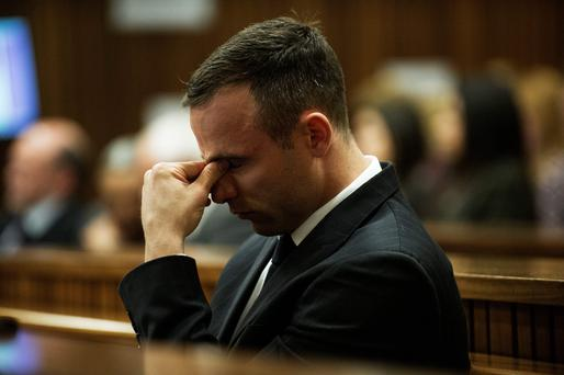 Oscar Pistorius reacts as he listens to forensic evidence being given in court in Pretoria