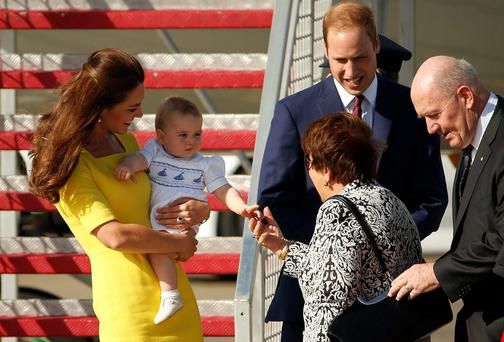 Prince William and his wife Kate, the Duchess of Cambridge, laugh as their son Prince George shakes the hand of Lynne Cosgrove, wife of the Governor-General of Australia Peter Cosgrove, after arriving in Sydney