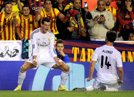 Gareth Bale (L) of Real Madrid celebrates beside Xabi Alonso after scoring Real's winner