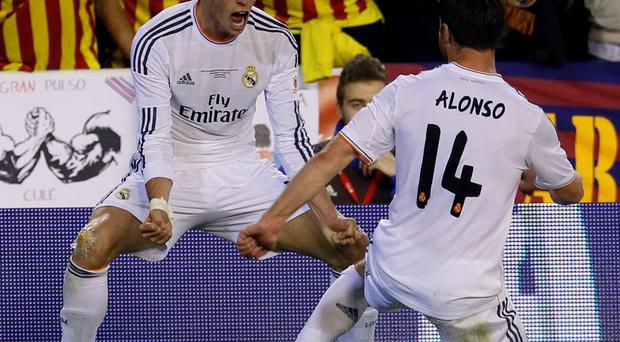 Real Madrid's Gareth Bale celebrates his goal with his teammate Xabi Alonso (R) during the Copa del Rey final