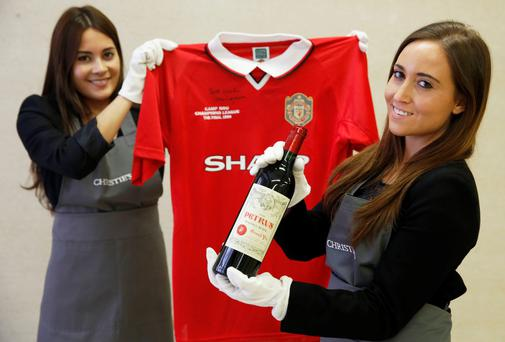 Christie's staff with a bottle of Petrus 1988 and a Manchester United retro Champions League shirt from 1999. Reuters