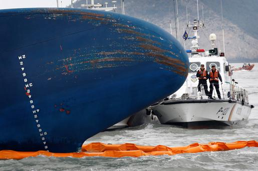 A vessel involved in search and rescue operations passes near the upturned South Korean ferry