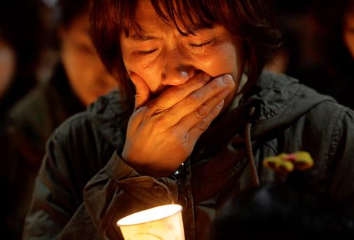 A woman offers prayers during a candlelight vigil for the missing passengers of a sunken ferry at Danwon High School in Ansan, South Korea. AP