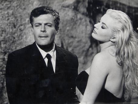 "Actors Marcello Mastroianni (L) and Anita Ekberg perform a scene in the epic film ""La Dolce Vita"" by director Federico Fellini at Cinecitta Studios in Rome in 1959."