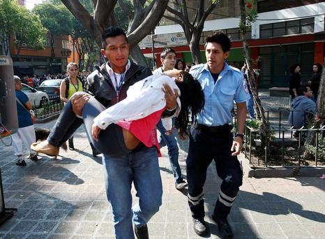 A man carries a young woman who fainted after she and co-workers were evacuated following an earthquake in Mexico City April 18, 2014. The magnitude 7.2 quake was centred in the south-western state of Guerrero, close to the Pacific beach resort of Acapulco, the U.S. Geological Survey (USGS) said. Some residents of the capital ran outdoors in their pajamas after the quake. Electricity was cut off in parts of the city and some residents said paintings fell off the walls while small parts of masonry crumbled inside apartment buildings. REUTERS/Bernardo Montoya