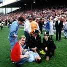 Liverpool's chief executive Peter Robinson, right, of the time watches as a fan is treated on the Hillsborough pitch in 1989