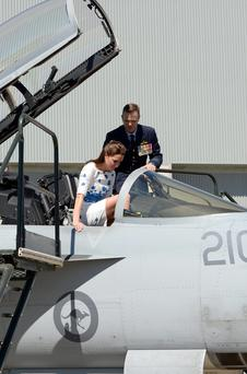 The Duchess of Cambridge climbs into the cockpit of an F/A-18F Super Hornet as the Duke and Duchess of Cambridge visit RAAF base Amberley