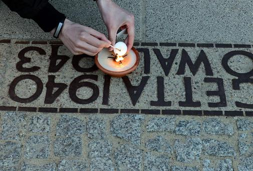 A man lights a candle in a place where during WWII a border wall stood separating the Warsaw ghetto from the rest of the town, in Warsaw.
