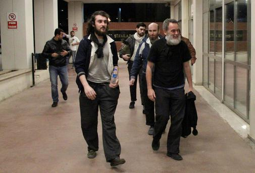 French journalists Edouard Elias (front L), Didier Francois (R), Nicolas Henin (2nd R, background) and Pierre Torres (3rd R, background) arrive at a hospital in Sanliurfa, southeastern Turkey. The four French journalists, held hostage in Syria since June, were found by Turkish soldiers on its border with Syria. They were found in Sanliurfa province, blindfolded with their hands bound.