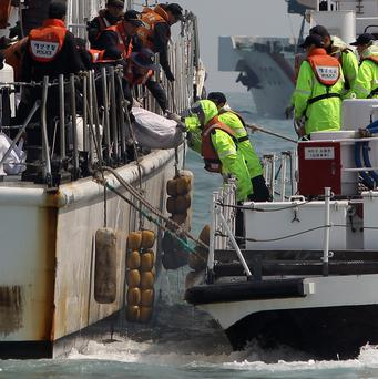 The South Korean coast guard carry a victim of the sunken ferry at the site of the ferry off the coast of Jindo Island on April 20