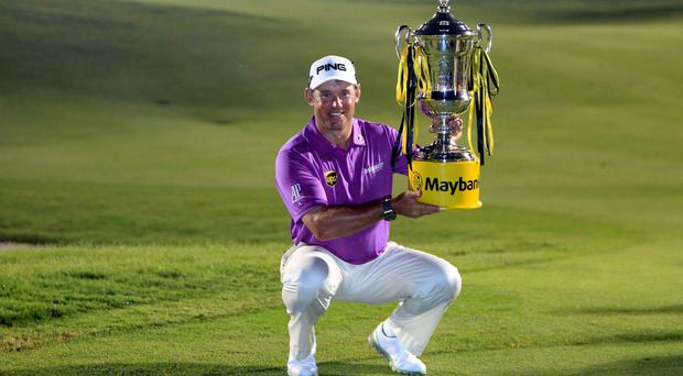 Lee Westwood of England poses for photographers with his trophy after winning the Malaysian Open